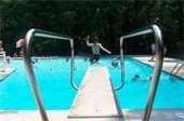 Boy jumping off diving board into a pool