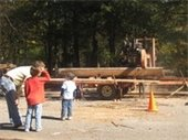 kids looking at wood being loaded on a trailer