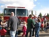 people looking at fire truck on display