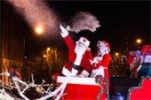 Santa Claus waving to a parade crowd