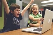children cheering in front of laptop