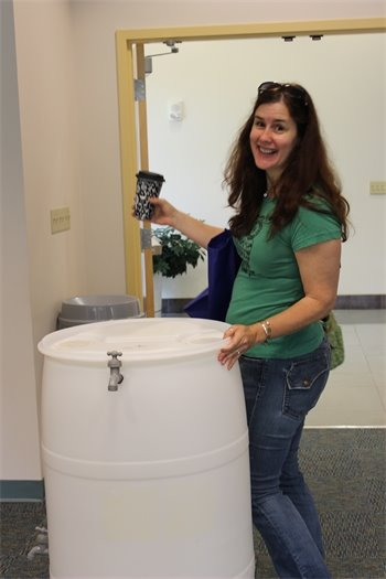 A previous workshop participant proudly shows off her new rain barrel.