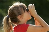 Young girl looking through binoculars