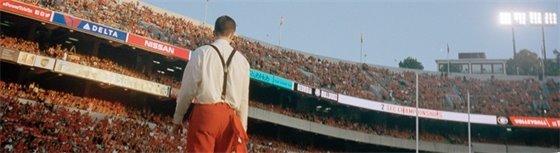 figure in suspenders in a sports stadium
