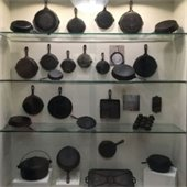 Display case featuring many cast iron skillets and cooking tools