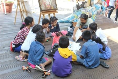 Made Bayak demonstrates artmaking techniques for a group of children