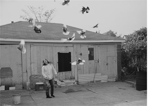 Picture of young person in front of house with pigeons flying around