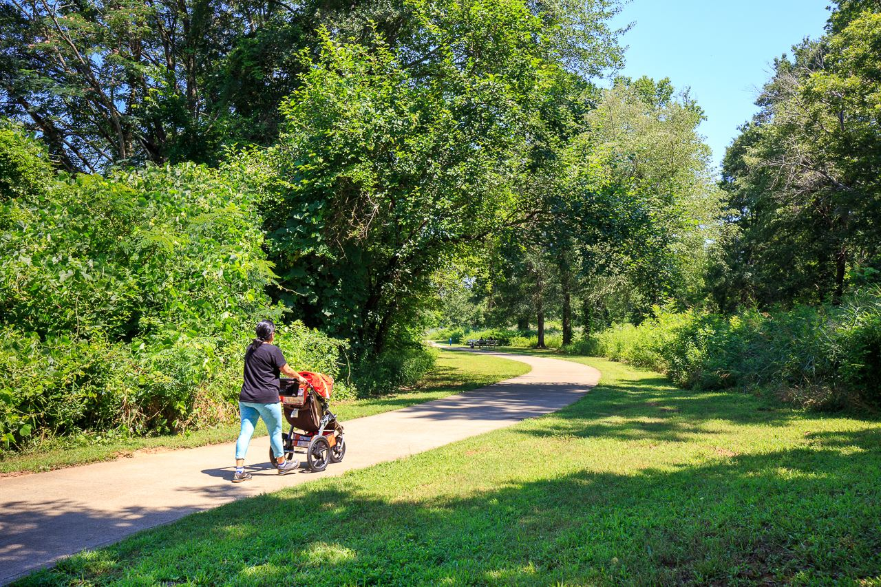 Woman walking with stroller on paved trail