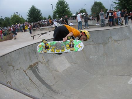 Skater pulls a front side grab over the bowl at the skate park