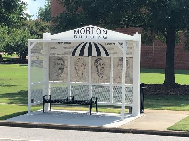 "white bus shelter with black bench and ""morton building"" on top"