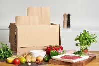 A cardboard box with tomatoes, meat, onions, and other raw foods on the counter to use for a meal