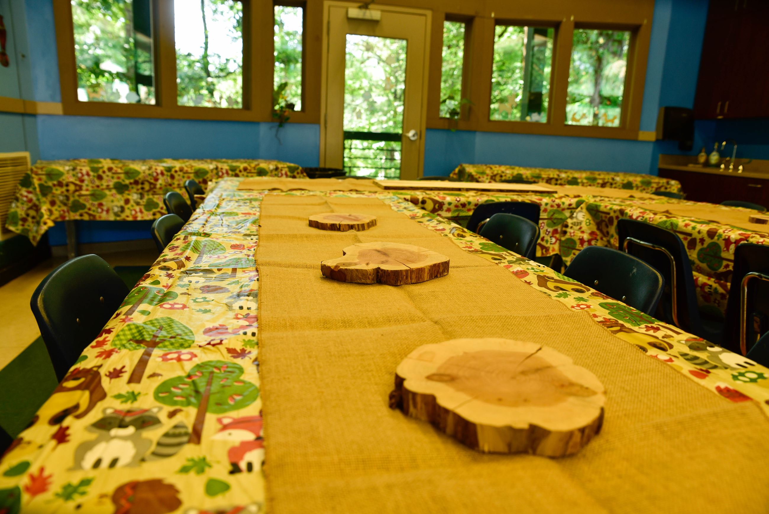 decorated table with woodland creature tablecloth, burlap runner, and cut wooden trivets