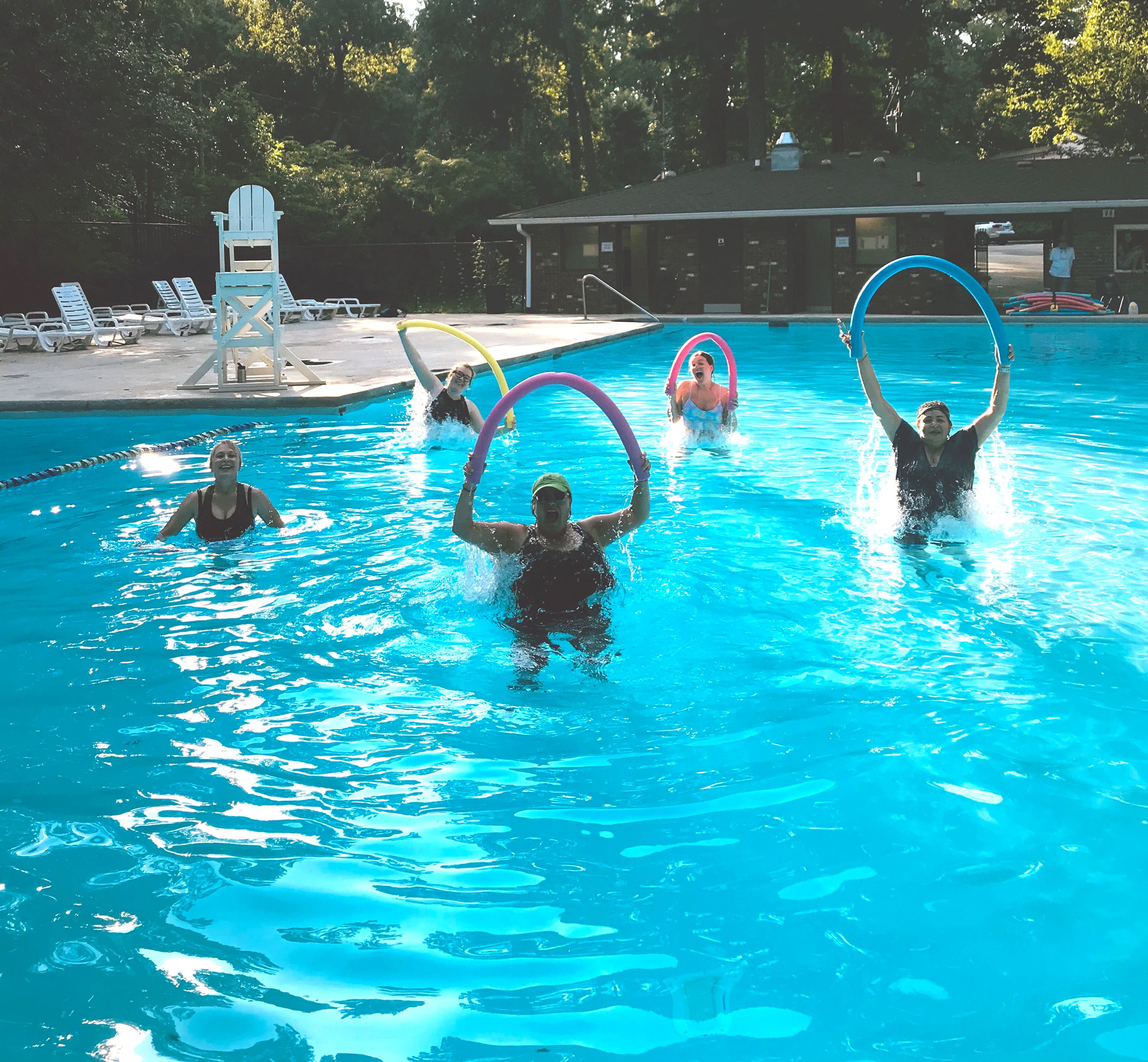 A group of ladies participate in water aerobics in the swimming pool.