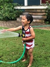 Child sprays hose and smiles.