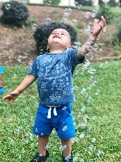A small child enjoys bubbles.