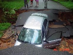 Washed out street with car in hole